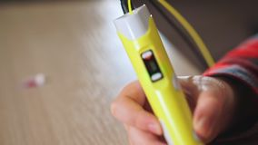 De tienerjongen neemt een stuk van geel ABS plastiek in een 3D pen op Hij creeert een plastic 3D cijfer stock videobeelden