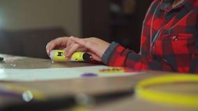De tienerjongen neemt een stuk van violet ABS plastiek in een 3D pen op Hij creeert een plastic 3D cijfer stock videobeelden