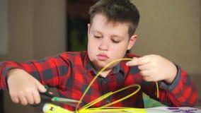De tienerjongen snijdt een stuk van geel ABS plastiek voor 3D pennen af Hij creeert een plastic 3D cijfer stock footage
