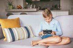 De tienerjongen speelt emotionaly op de spelconsole aan smartphone wordt verbonden die stock fotografie