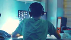 De tienerjongen speelt online spel op computer via Internet-monitor in hoofdtelefoons de tienermens speelt een videospelletje bij stock videobeelden