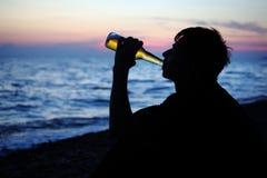 De tienerjongen van het silhouet het drinken bier op zeekust royalty-vrije stock fotografie