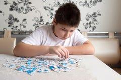 De tienerjongen verzamelt raadsels bij lijst royalty-vrije stock afbeeldingen