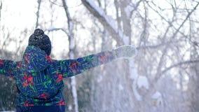 De tienerjongen werpt sneeuw in het de winterbos stock videobeelden
