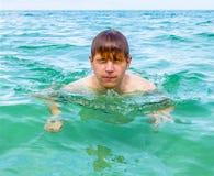 De tienerjongen zwemt in de oceaan en heeft zoutwater in de ogen stock foto
