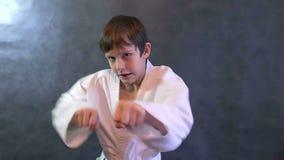 De tienerkaratejongen in kimonostrijd overhandigt golvende vuisten langzame motie stock videobeelden