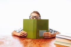 De tienerkerel viel in slaap zitting met boeken, studentenslaap bij Bureau in Studio op witte achtergrond stock afbeelding