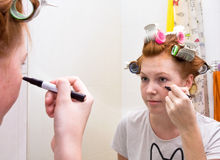 De tienermeisje dat van de roodharige make-up doet stock afbeeldingen
