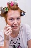De tienermeisje dat van de roodharige make-up doet royalty-vrije stock afbeeldingen