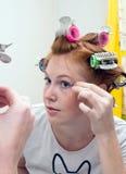 De tienermeisje dat van de roodharige make-up doet royalty-vrije stock foto