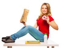 De tienermeisje die van de school donuts eten royalty-vrije stock fotografie