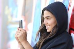 De tienermeisje van de schaatserstijl gelukkig lezen haar slimme telefoon royalty-vrije stock afbeelding