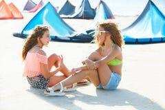 De tienermeisjes die van de vliegerbranding in de zitting van het de zomerstrand spreken Royalty-vrije Stock Afbeeldingen
