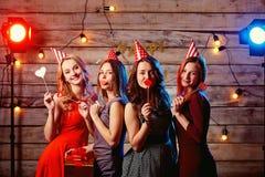 De tienermeisjes van de verjaardagspartij Jonge meisjes in hoeden en steunen Stock Afbeelding