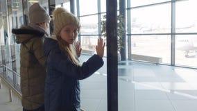De tienermeisjes wacht hun vlucht bekijkend panoramisch venster in luchthaventerminal stock footage