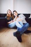 De tienerpaar het letten op komedie toont op TV Stock Foto