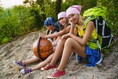 De tienerreizigers die met rugzakken op kustzwerflust zitten reizen concept stock afbeeldingen