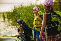 De tienerreizigers met rugzakken die zich op kustzwerflust bevinden reizen concept stock afbeelding