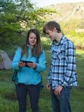 De tieners bekijken het aanrakingsscherm Stock Foto