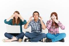 De tieners bij 3 Wijze Apen stellen Holdingsgadgets Royalty-vrije Stock Afbeelding