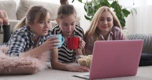 De tieners die op media letten stellen thuis op laptop tevreden terwijl het hebben van snacks stock footage