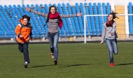 De tieners en de jongen genieten van aan het lopen Stock Foto