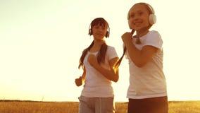 De tieners in hoofdtelefoons zijn bezig geweest met jogging die, die en tijdens fysieke inspanning lachen glimlachen Langzame Mot stock video