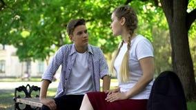 De tieners koppelen het strijdig zijn, zittend bij parkbank, conflict dat op jaloersheid wordt gebaseerd stock afbeeldingen
