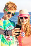 De tieners maken zelfportret en het luisteren het luisteren muziek op de overzeese achtergrond Royalty-vrije Stock Afbeelding