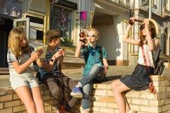 De tieners met rente en verrassings het letten op filmfoto verbiedt, de achtergrond van de stadsstraat royalty-vrije stock foto's