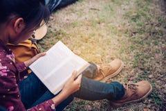 De tieners ontspannen door boeken op het gebied van de tentpicknick in t te lezen royalty-vrije stock fotografie