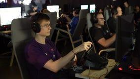 De tieners spelen in het autoras met het wiel van een spelconsole stock videobeelden
