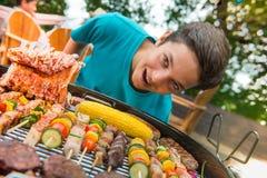 De tieners tijdens een barbecue bij familie tuinieren BBQ Royalty-vrije Stock Afbeelding