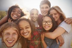 De tienerschoolvrienden die aan camera glimlachen, sluiten omhoog stock foto