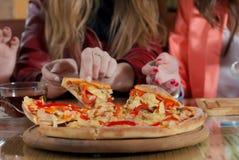 De tijd en het meisjesvrienden die van de pizza goede tijd hebben Royalty-vrije Stock Afbeeldingen