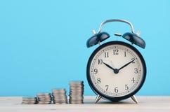 De tijd is Geldconcept, stapelend muntstukken en wekker op houten stock foto