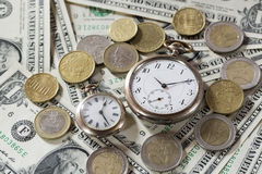 De tijd is het concept van geldfinanciën met oude uitstekende klokken, dollarrekeningen en euro muntstukken Stock Foto's