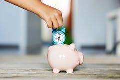 De tijd is kostbaar, sparen tijdconcept met spaarvarken en blauwe wekker in meisjehand royalty-vrije stock afbeeldingen