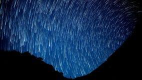 De tijd-tijdspanne van de sterrensleep in de voorgrond van silhouetberg stock footage