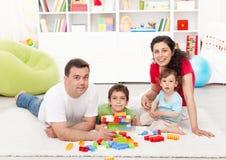 De tijd van de familie - jonge ouders met twee jonge geitjes het spelen Stock Foto's