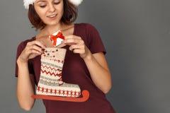De tijd van Kerstmis Jonge die vrouw in santahoed op grijs wordt geïsoleerd die gift zetten in vleetlaars die opgewekt close-up g stock afbeelding