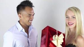 De tijd van Kerstmis Jonge mens die een gift aanbieden aan zijn meisje stock video
