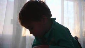 De tijd van zonsondergang Een klein kind bekijkt de camera dichtbij het venster en glimlacht De close-up van het gezicht De zon`  stock videobeelden