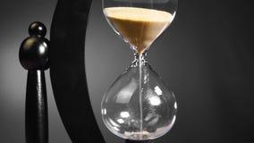 De tijd, de zandloper draait de hand en begint met de aftelprocedure van vijf minuten in zwart-witte schaduwen stock videobeelden