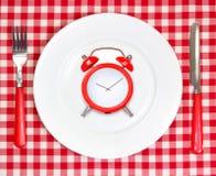 De tijdconcept van de dieetlunch Rode wekker op ronde witte plaat Royalty-vrije Stock Afbeeldingen