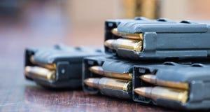 De tijdschriften met kogels van vuurwapen putted op houten lijst Sluit omhoog mening, vage achtergrond stock fotografie