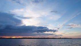 De tijdspanne van de zonsondergangtijd met het bewegen van wolken langs meer stock video