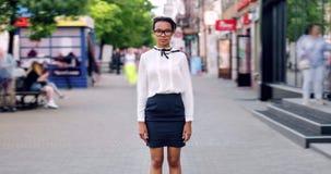 De tijdspanne van de uitzoomentijd van mooie Afrikaanse Amerikaanse vrouw status in voetstraat stock videobeelden