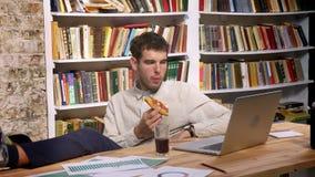 De tijdtijdspanne van plezierig Kaukasisch mannetje zit met zijn benen op Desktop en bekijkt computer terwijl het drinken van cok stock videobeelden