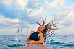 De tik lang nat haar van het surfermeisje met plonsen in lucht stock afbeeldingen